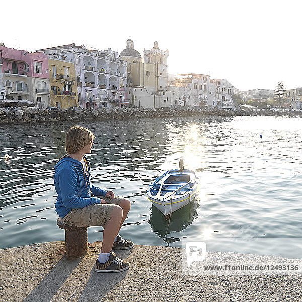 Teen boy sits in harbour in front of village