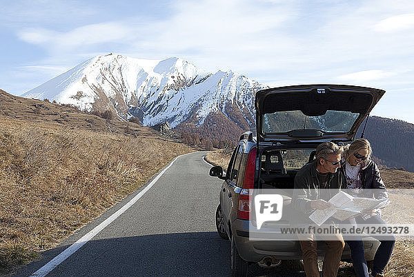 Couple look over map from trunk of car on mountain road