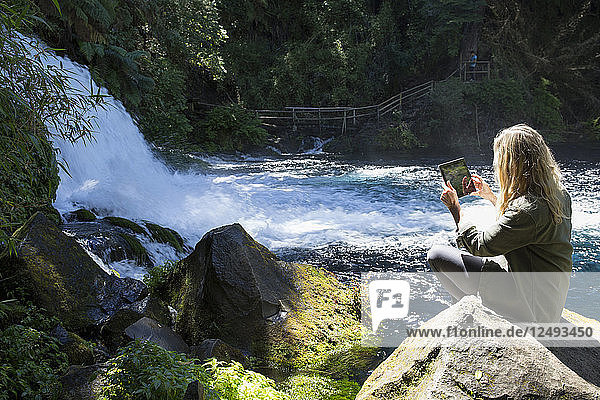 Mature woman takes photo with tablet of mountain waterfall