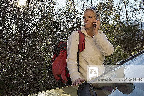 Mature woman hiker talks on phone by car in forest