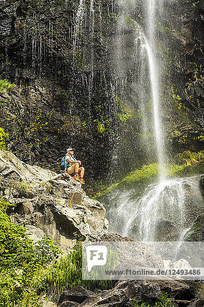 A woman resting on a rock while hiking below Treasure Falls on Wolf Creek Pass near Pagosa Springs  Colorado