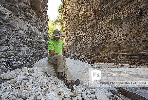 Senior Man Sitting On Rock In A Narrow Dry Canyon Of Steep Layered Rock Walls