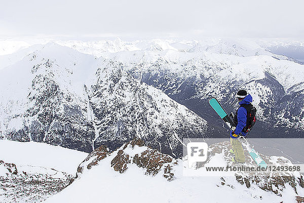 A Skier Stands On A Rocky Mountain Overlooking The Andes Mountains From Cerro Catedral In Argentina