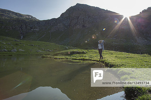 Woman watches sunrise by mountain pond
