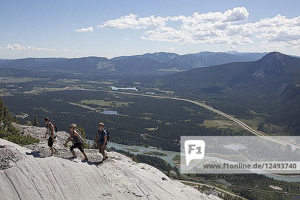Elevated view of three hikers on ridgeline