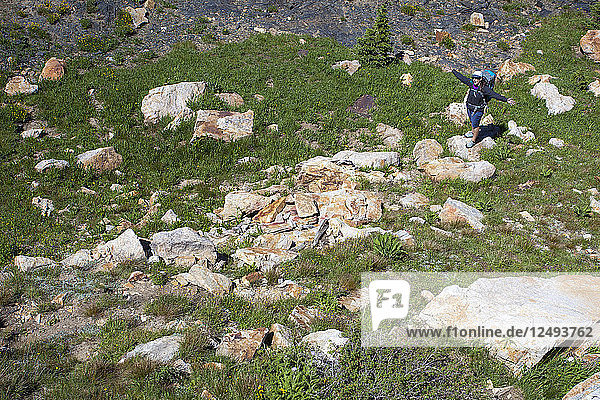 A women stops and spreads here arms while hiking down from a rock climb in Little Cottonwood Canyon  Utah.