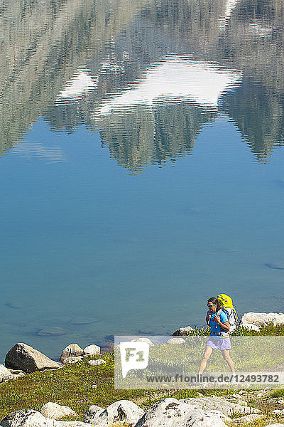 A woman hiking along trail past mountains reflected in the Upper Lake of Titcomb Basin in the Wind River Range  Bridger Teton National Forest  Pinedale  Wyoming.