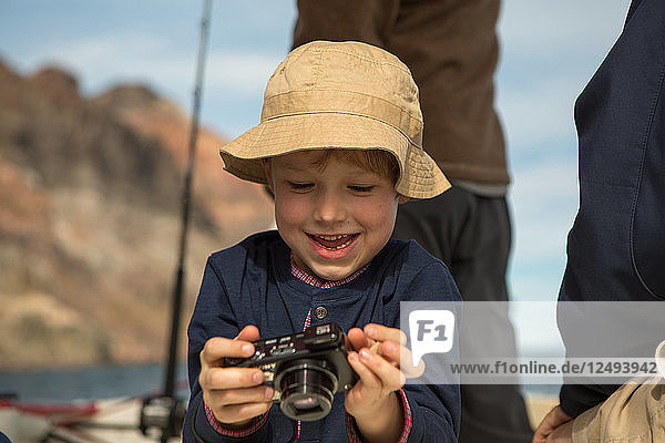 Young boy looks through camera on boat