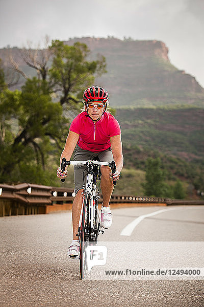 Women road cyclist rides her road bike  on Co Rd 38 E heading west  just west of Horsetooth Mountain Park.