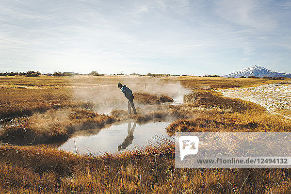 A young woman in a blue coat leans to peer into a steaming hot spring in a vast  dry  marshy landscape.