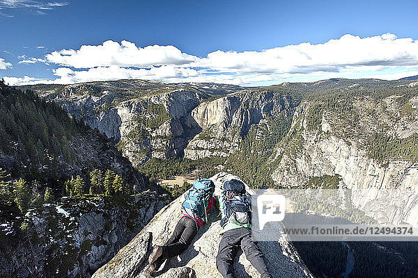 Two backpackers lay on a rock cliff at Glacier Point overlooking Yosemite National Park.