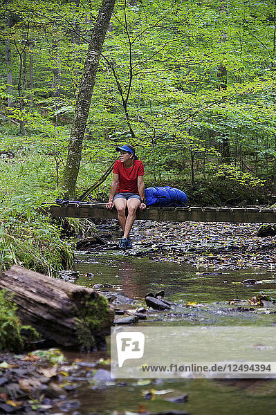 Woman backpacker hiking on the West Rim Trail in Tioga State Park of north central Pennsylvania September 2011. The 30-mile long trail overlooks Pine Creek Gorge and is considered the Grand Canyon of Pennsylvania.