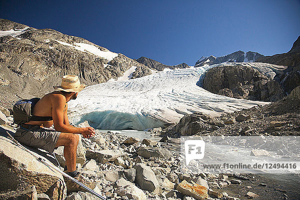 A hiker looks up toward Wedge Glacier as it melts in the mid day sun in Garibaldi Provincial Park.