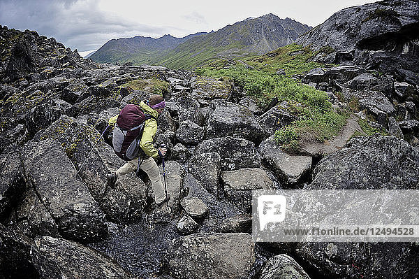 Woman hiker navigates a boulder field during a backpacking trip to Reed Lakes in the Talkeetna Mountains near Palmer  Alaska August 2011.