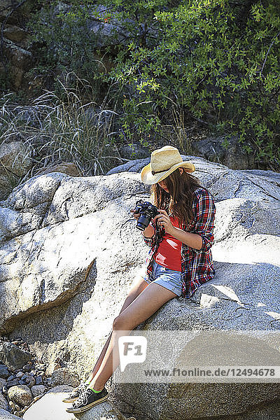A fit young woman in a cowboy hat takes photographs in a forested natural environment.