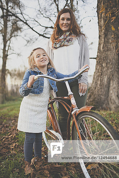 A mother and daughter pose with an old fashioned bicycle.
