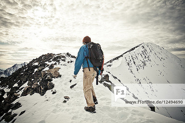 A backpacker hikes a rocky rideline toward the summit of Frosty Mountain in Manning Provincial Park  BC  Canada.