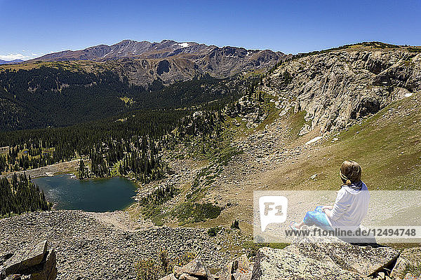 A young female sits on a rock edge in the mountains over looking a lake below in Colorado
