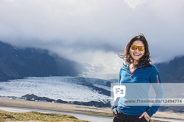 Portrait Of A Smiling Woman In Front Of A Glacier