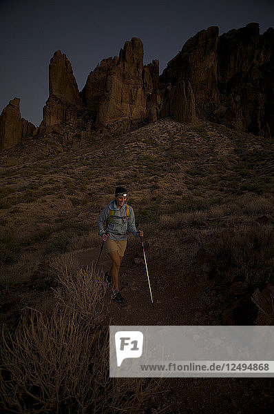 Woman hikes at night by headlamp on the Treasure Loop Trail in Lost Dutchman State Park near Phoenix  Arizona November 2011. The camp overlooks the spires of the Superstition Mountains.