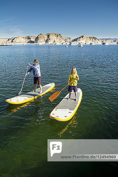 A mother and daughter paddleboarding on Lake Powell  Wahweap Marina  Glen Caynon National Recreation Area  Page  Arizona.