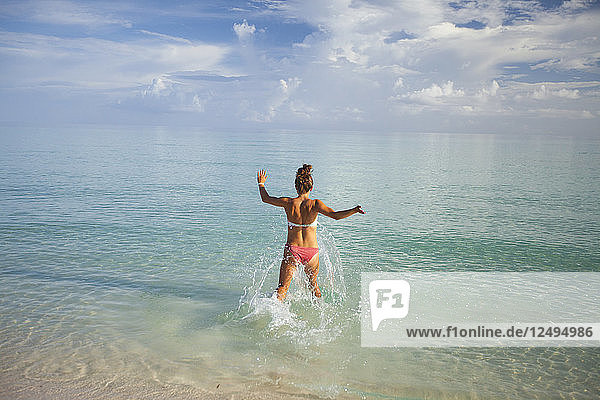 A young woman runs into shallow turquoise water while on vacation in Cayo Coco  Cuba.