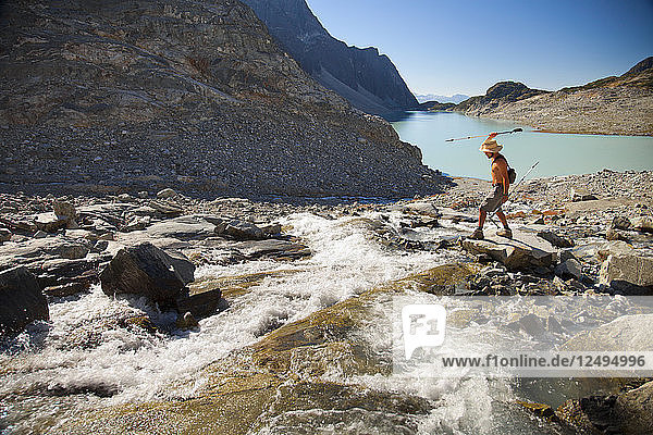 A shirtless hiker attempts to spear fish out of a river with a trekking pole in the Wedgemount Lake area of Garibaldi Provincial Park.