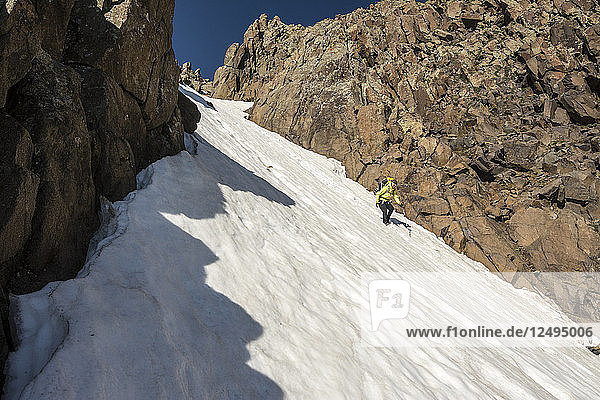 A Woman Descending A Snow Slope While Hiking On Blaine Peak Below Mount Sneffels