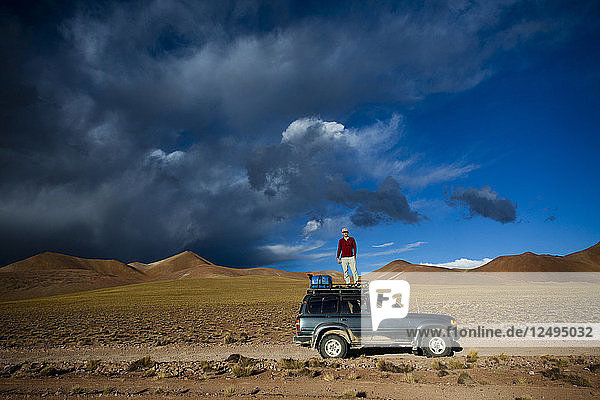 A man stands on the roof of his truck to take a photo of the dramatic sky at sunset near the Salar de Uyuni  Bolivia.