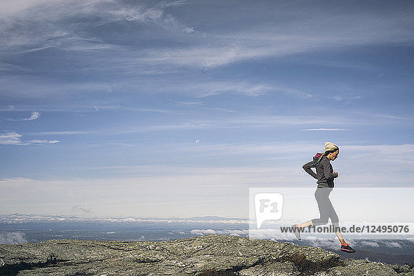 Woman Running On A Rocky Ridgeline Of Mount Mansfield  Vermont