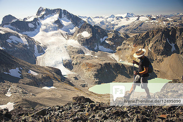 A hiker crosses a rocky ridge near Mount Cook with views of Wedge Mountain and Wedgemount Lake  a part of Garibaldi Provincial Park  seen in the backdrop.