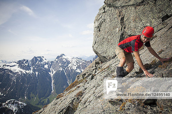 A climber carefully crosses a steep rock slab near the summit of Trio Peak  British Columbia  Canada.