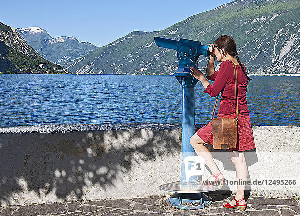 Woman looking through telescope out to the Garda Lake