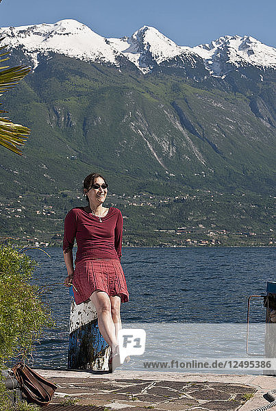 Woman sitting at the port in Limone at the Garda Lake in north Italy