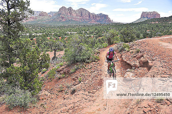 Woman rides the Templeton Trail in South Sedona  Arizona. Templeton Trail rides over slickrock of the Cathedral Rock with views of Courthouse Butte across the way.