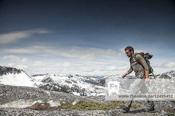 A backpacker hikes over granite rock in a sub-alpine terrain.