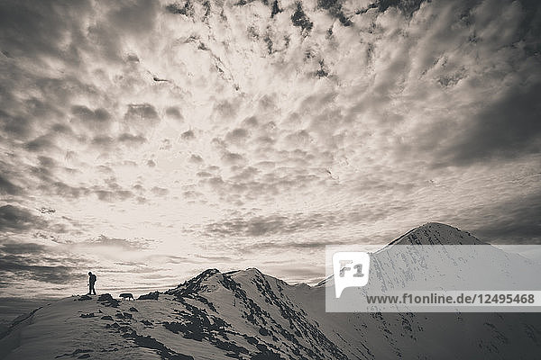 A backpacker and his dog hike a rocky ridgeline toward the summit of Frosty Mountain in the North Cascade Mountain Range.