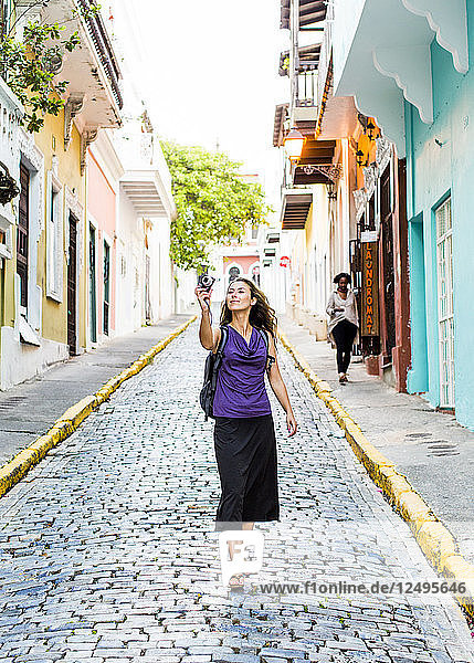 Young Woman Taking Picture Of Cobblestone Street Surrounded By Colourful Buildings
