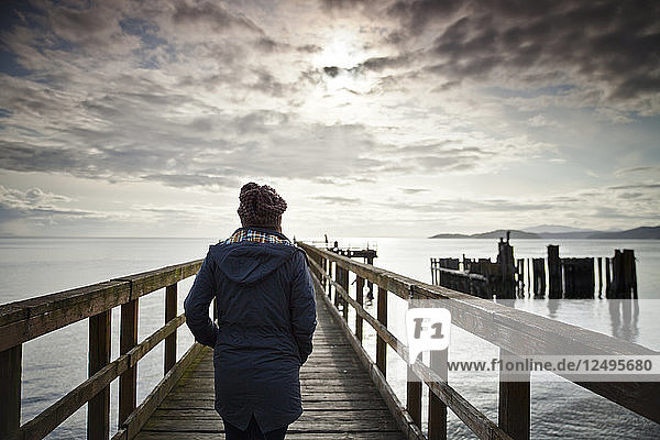 A woman wearing a blue coat and knited hat walks towards the end of the Davis Bay Pier in Secelt  B.C.  Canada.