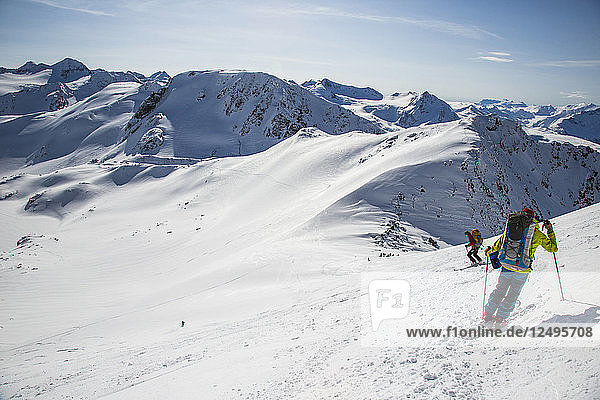 Skiers at the top of a mountain descend a wide open bowl in Whistler  British Columbia  Canada during the Spearhead Traverse.