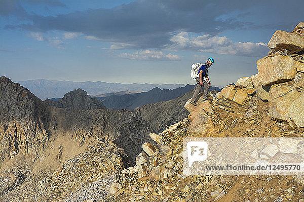 A man negotiating the ridgeline along the Evolution Traverse  John Muir Wilderness  Kings Canyon National Park  Bishop  California.