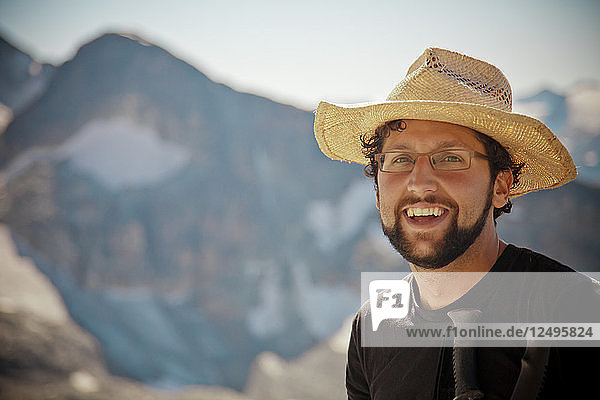 Portrait of a bearded hiker wearing a straw hat and glasses.