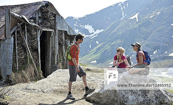 Hikers stop at an old shack on the trail to Gold Cord Lake in Independence Mine State Historical Park at Hatcher Pass  Alaska June 2011. The half-mile trail leads to an alpine lake above the historic gold mine near Hatcher Pass.