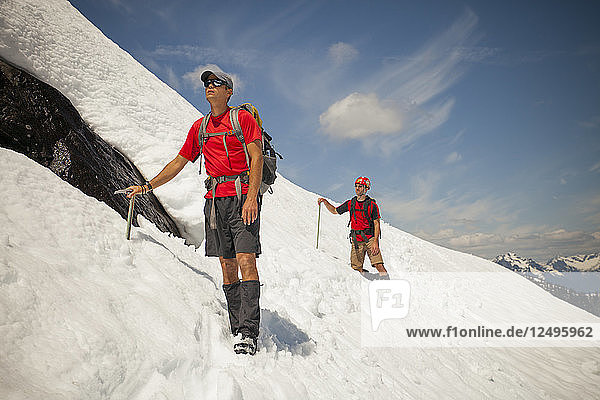 Two climber cross a snowfield high in the mountains of British Columbia  Canada.
