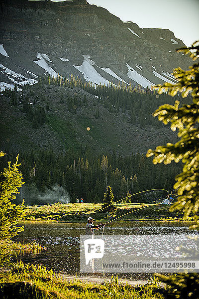 A fly fisherman in a high alpine lake at sunset in Yampa  Colorado.