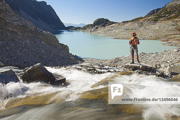A shirtless hiker stands beside a river as it rushes into Wedgemount Lake in Garibaldi Provincial Park.