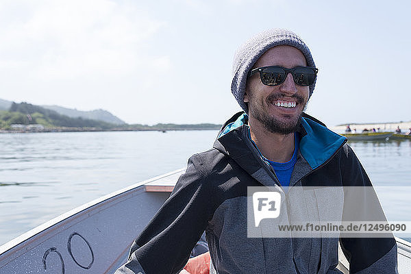 Young male adult smiles while riding in a small crabbing boat on the Oregon coast