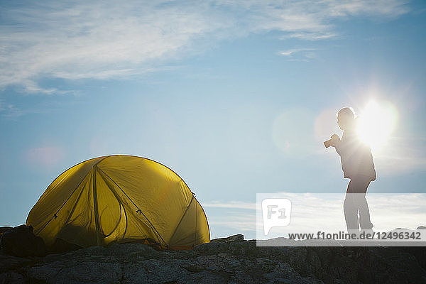 Silhouette of a photographer standing beside his tent shortly after sunrise.