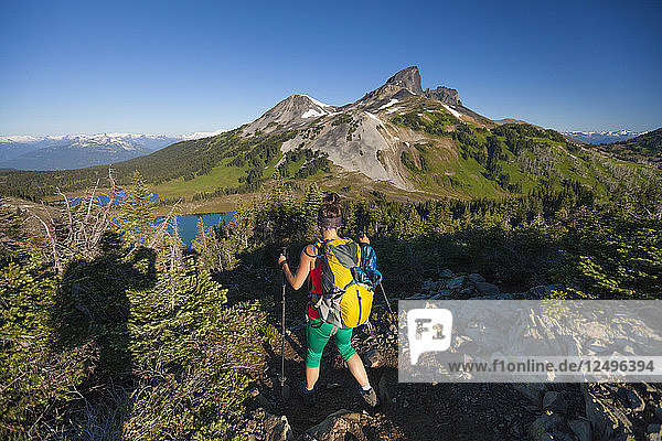 A photographer takes a picture of a young woman backpacking on the Panorama Ridge Trail with Black Tusk Mountain in the background in Garibaldi Provincial Park  British Columbia  Canada.