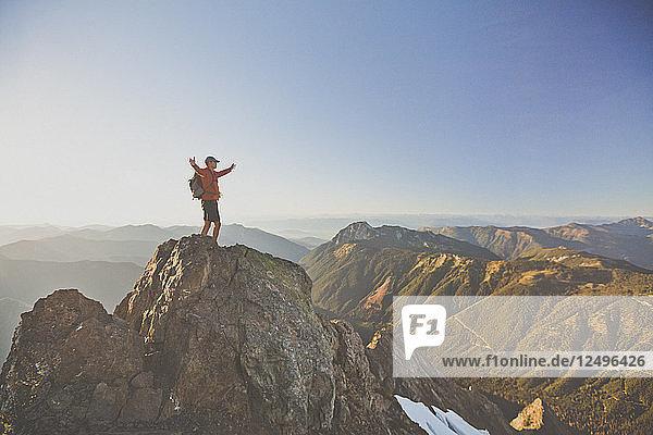 Male Backpacker Standing On The Summit Of Tomyhoi Peak